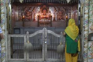 A woman looking at the idols of Jain teachers in Jamnagar, Gujarat.