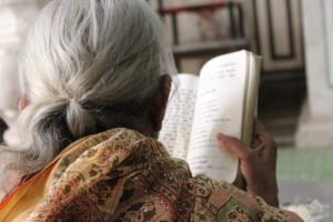 A woman reciting mantras from a Sanskrit book in Jaipur, Rajasthan.