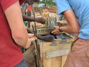 The supports for the A frames (which would hold the timber structure of the ground and so protect it from termites) had to be placed into the foundation as it was being poured, which took patience and as much precision as can be achieved with a tight piece of string and a spirit level.